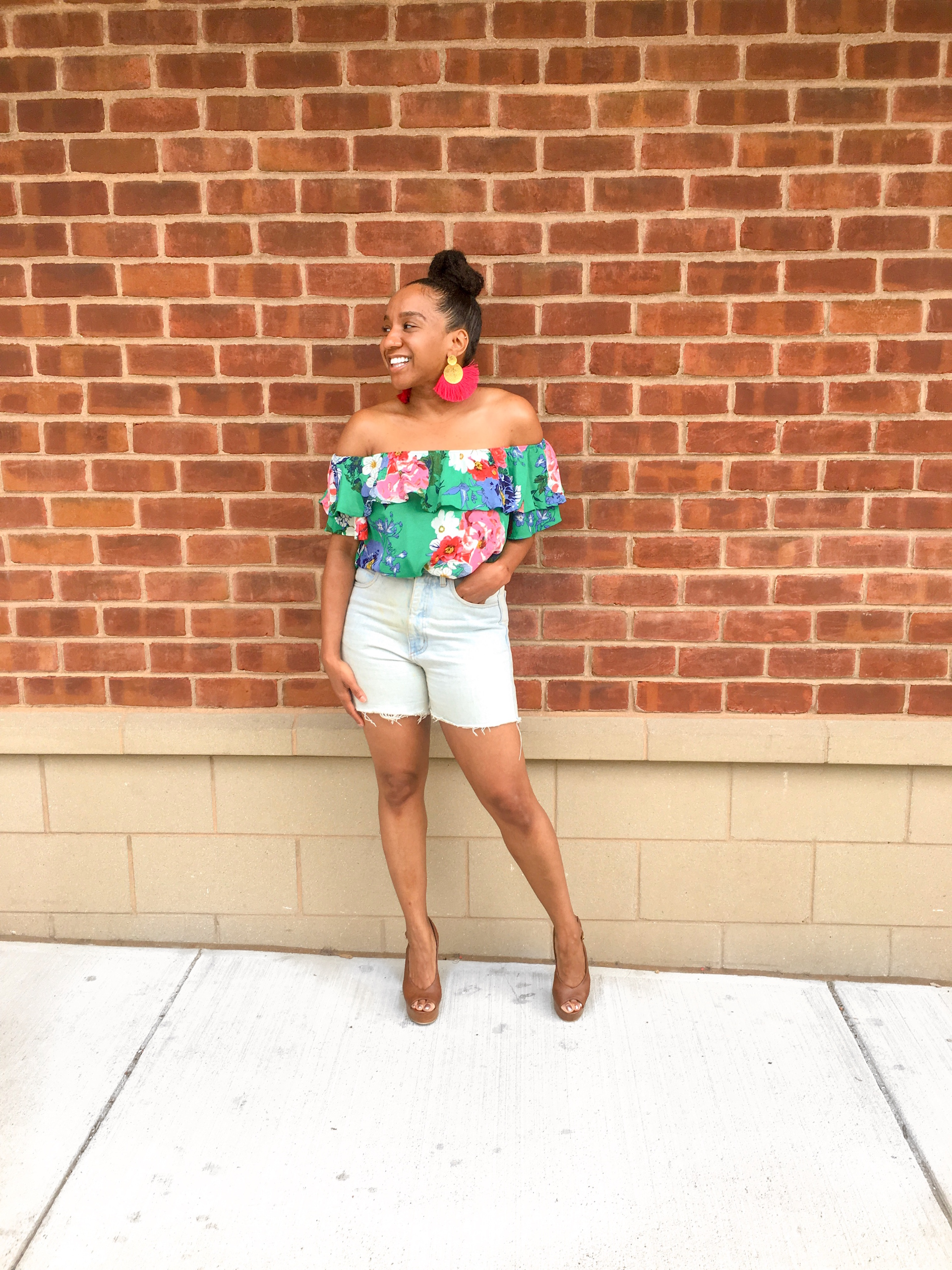 Tatiana in floral off the shoulder top against brick wall